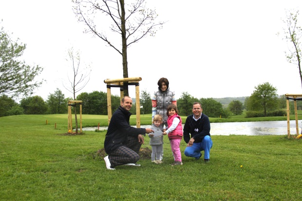 Geschäftsführer Michael Ogger (links) vom GC Velbert-Gut Kuhlendahl übergibt die Patenschaftsurkunde für die Eiche im Hintergrund an Familie Wormland (v.l.): Sissi, Tinca, Mutter Renate und Vater Nils (Foto: Stefan Mülders)