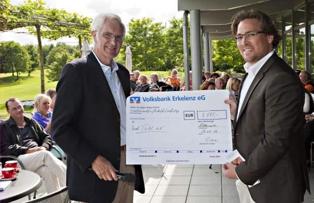 """Mit sichtbarem Stolz überreicht GC Wildenrath-Präsident Prof. Dr. Jochen Hilden den Scheck über € 2 555,00 an Marc Hölzle, den Vertreter des Fördervereins """"Tobi e.V."""""""