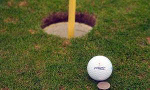 Golfball mit Münze als Marker